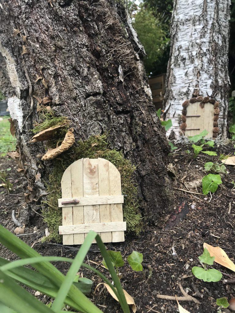 mini-porte de fée ou de lutin au pied d'un arbre