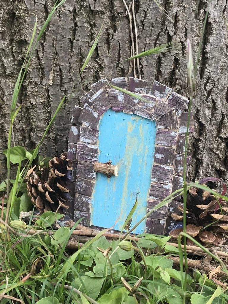 mini-porte en bois au pied d'un arbre